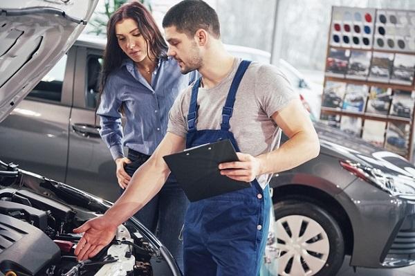 en kvinna och en bilmekaniker står vid en bil