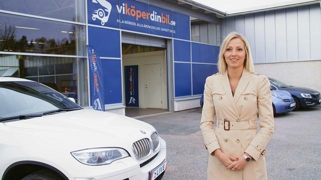 en kvinna står utanför en bilhandlare