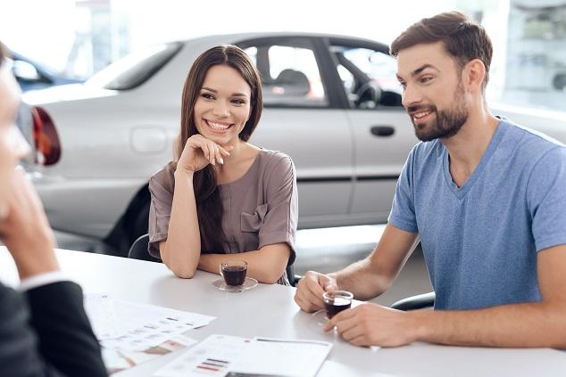 Ett par som vill får hjälp med papper som behövs vid en bilförsäljning